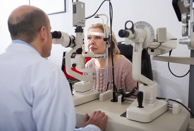 Patient getting eyes checked by eye health professional using a slit lamp